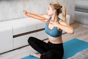 Frau zu Hause, die versucht, Gewicht zu verlieren und mit Gummiband zu trainieren foto