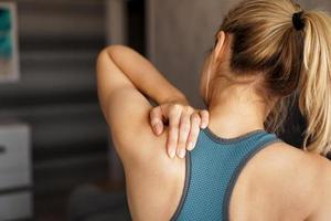 Konzept für Sportverletzungen. sportliches Mädchen, das Schmerzen im Nacken verspürt foto