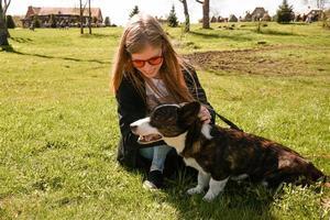 junge Frau mit roter Sonnenbrille spielt mit ihrem Corgi foto