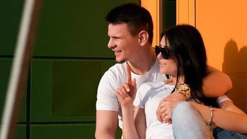 junges Paar, das in eine Richtung gegen helle Wand aus Gelb und Grün schaut foto