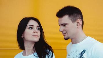 Porträt eines fröhlichen jungen Paares, das über gelbem Hintergrund steht foto