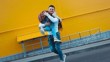 glücklicher Mann, der seine Freundin auf gelbem Hintergrund trägt foto