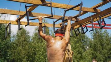 Mann, der während des Hindernislaufs im Bootcamp Hürden überwindet foto