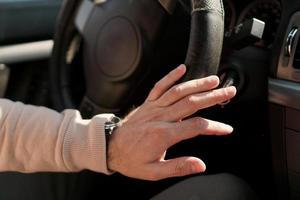 die Hand eines Mannes auf einem Lenkrad. schäbige Lenkradverkleidung in einem Auto. foto