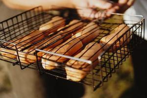 leckere Grillwürstchen auf dem Eisenrost ruhen foto