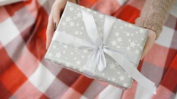 Weihnachtsgeschenke auspacken. Frau hält und öffnet Geschenke foto