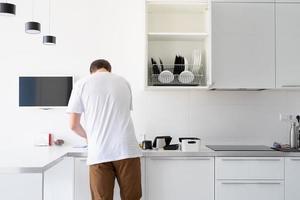 Mann im weißen T-Shirt beim Abwasch in der Küche foto