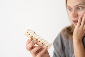Frau, die sich die Haare bürstet, die an Haarausfall leidet foto