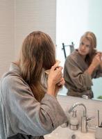 Frau bürstet sich die Haare und lächelt beim Blick in den Spiegel foto