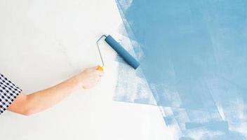 Mann färbt Wand blau mit einer Walze foto