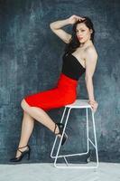 schöne Frau sitzt auf einem Stuhl auf grauem Hintergrund foto
