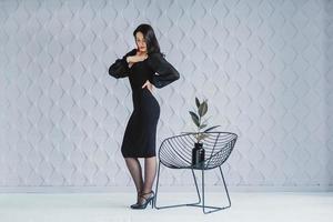 Mode brünette Frau trägt ein schwarzes Kleid in der Nähe des Stuhls foto