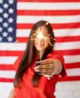 schöne Frau, die eine Wunderkerze auf uns Flaggenhintergrund hält foto