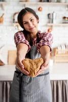 glückliche brünette Frau, die herzförmigen Teig in der Küche hält foto