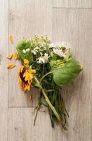 ein Strauß verwelkter Blumen auf dem Boden foto