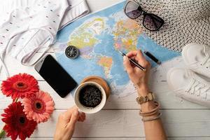 Frau von oben, die eine Reise plant, Kaffee trinkt und auf einer Karte zeichnet foto