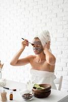 junge Frau, die mit einer Kosmetikbürste eine Spa-Gesichtsmaske auf ihr Gesicht aufträgt foto