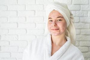 glückliche junge Frau, die Gesichtspeeling auf ihrem Gesicht anwendet foto