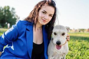 schöne junge frau, die im gras sitzt und ihren hund im park umarmt foto