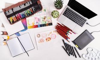 Künstlerarbeitsplatz mit Laptop, Tablet und Zeichenwerkzeugen foto