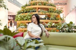 junge Frau sitzt auf der Couch im Einkaufszentrum foto