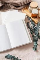 geöffnetes Buch, Kerzen und Eukalyptusblätter. Mock-up-Design foto