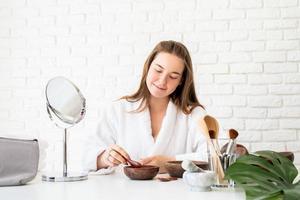 Frau mit Bademänteln, die Spa-Behandlungen mit Naturkosmetik macht foto