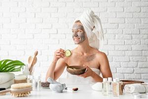 Frau, die mit einer Kosmetikbürste eine Spa-Gesichtsmaske auf ihr Gesicht aufträgt foto