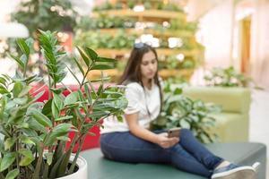 Frau auf der Couch im Einkaufszentrum und schaut auf das Telefon foto