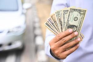Geschäftsmann, der Bargeld in der Hand auf Autohintergrund hält. foto