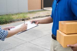 Nahaufnahme von Frauenhände unterschreiben, um ihr Paket vom Zusteller zu bekommen. foto