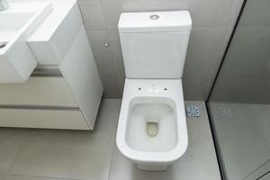 Blick von oben auf die saubere weiße Toilettenschüssel in einem modernen Badezimmer. foto