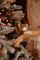 ein Kind, das Weihnachtskugel hält. Weihnachtskarte foto