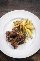 würzige BBQ-Barbecue-Schweinerippchen mit Wedges Pommes frites foto