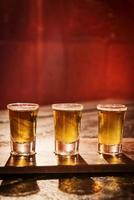 Whisky-Shots im gemütlichen roten Bar-Interieur foto