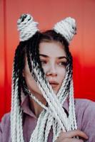Porträt des schönen coolen Mädchens über roter Wand foto