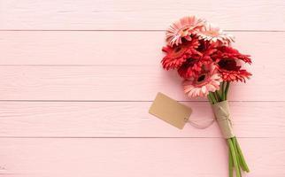 rote Gerbera-Gänseblümchen-Blumen und leeres Basteletikett auf rosa foto