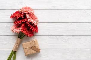 Rote Gerbera-Gänseblümchen-Blumen und Bastel-Geschenkbox mit Label-Anhänger foto