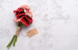 rote Gerbera-Gänseblümchen-Blumen und Basteletikett foto