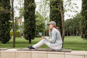 Frau im Freien telefoniert mit ihrem Handy foto