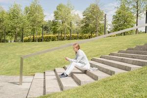 Frau, die auf ihrem Handy eine SMS schreibt und auf der Treppe im Park sitzt foto