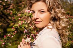 romantische junge Frau im Frühlingsgarten unter Apfelblüte. foto