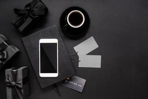Schwarzes Smartphone, Preisschilder, Kaffee und Geschenke Draufsicht auf Schwarz foto