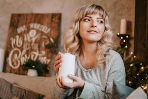 junge Frau, die lächelt, während sie eine Kerze hält, die Weihnachten feiert foto