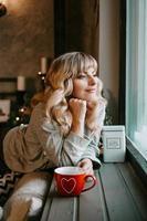 junge Frau mit Tasse Tee im gemütlichen Weihnachtsinterieur foto