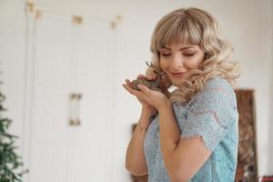 Holzhirsch in den Händen einer jungen Blondine foto