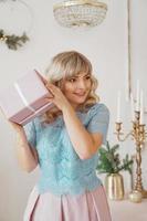 schöne junge frau mit elegantem stil mit rosa weihnachtsgeschenk foto