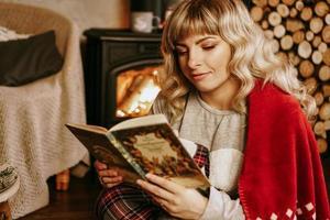 glückliche junge frau, die buch vor weihnachtsinnenraum liest foto