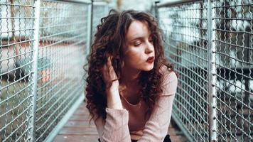 Modeporträt einer trendigen jungen Frau, die in der Nähe des Netting Rabitz sitzt foto