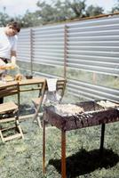 Mann grillt Kebabs am Spieß foto